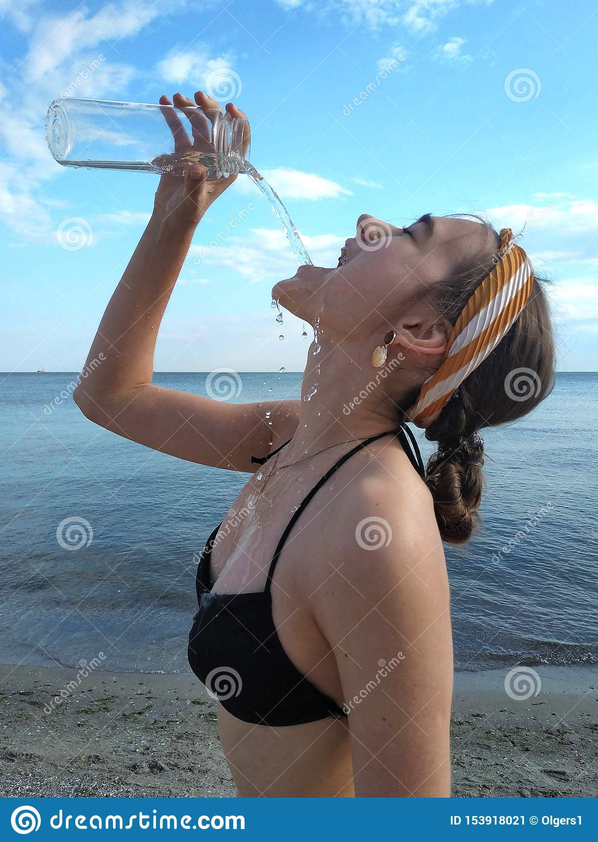 A jovem mulher bonita bebe a agua potável da garrafa
