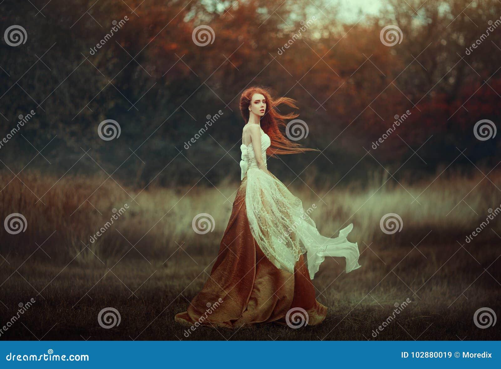 Jovem mulher bonita com cabelo vermelho muito longo em um vestido medieval dourado que anda com o vermelho da floresta do outono