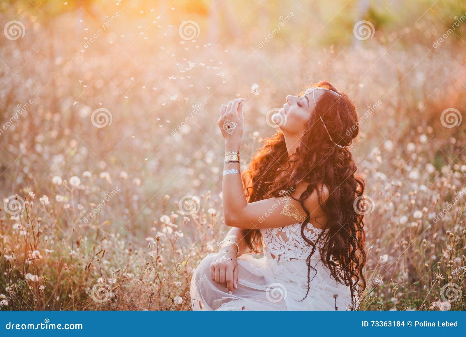 Jovem mulher bonita com o cabelo encaracolado longo vestido no vestido do estilo do boho que levanta em um campo com dentes-de-le