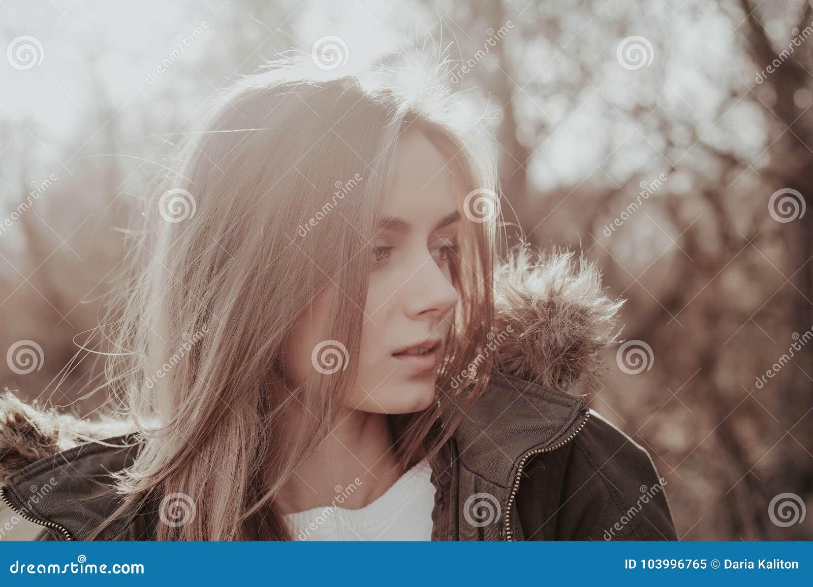 Jovem mulher bonita com o cabelo louro que olha lateralmente