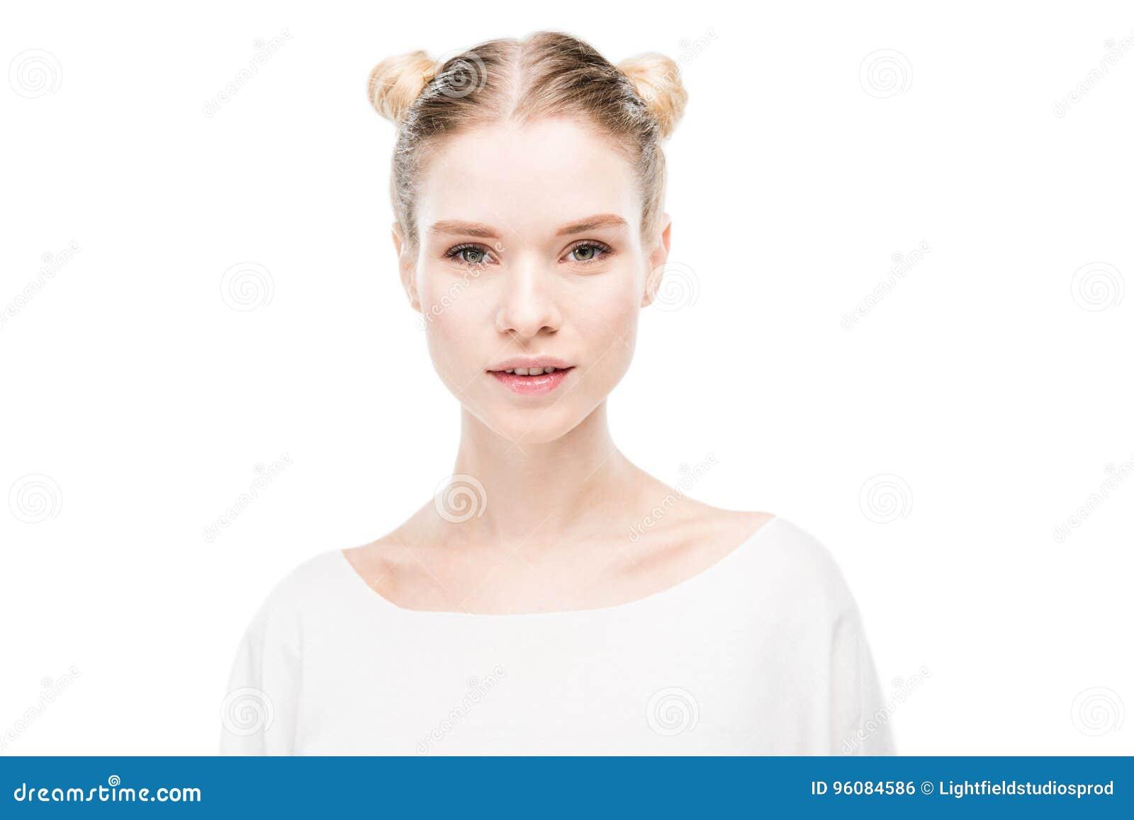 Jovem mulher bonita com os bolos do cabelo que olham a câmera