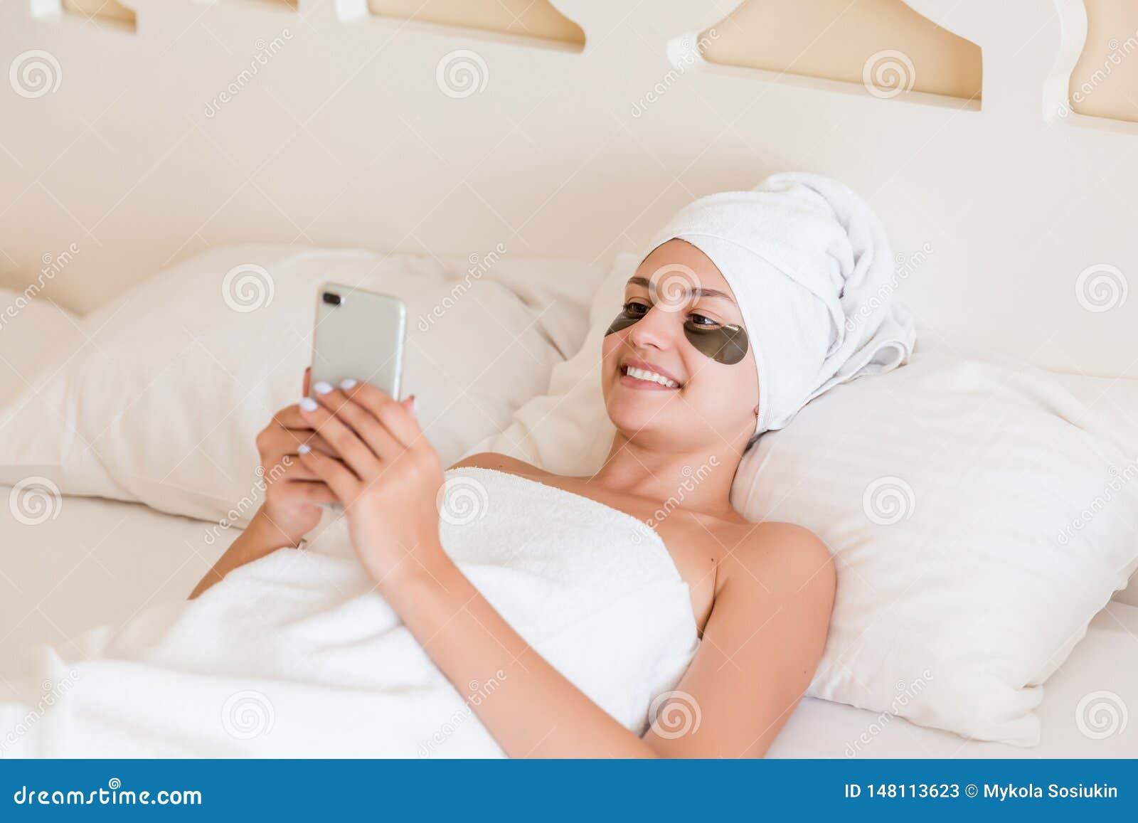 Jovem mulher bonita com os remendos inferiores do olho e telefone celular da utiliza??o no roup?o que encontra-se na cama Menina