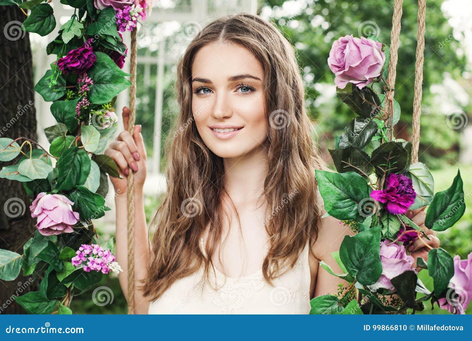 Jovem mulher bonita com Rose Flowers Outdoors