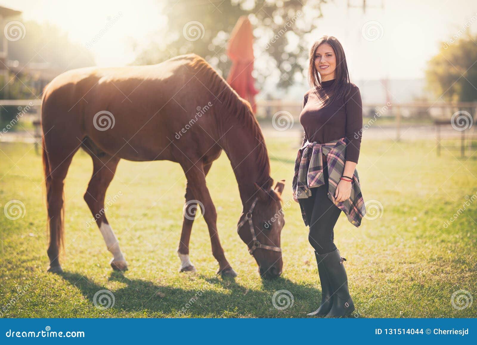 Jovem mulher bonita com seu cavalo