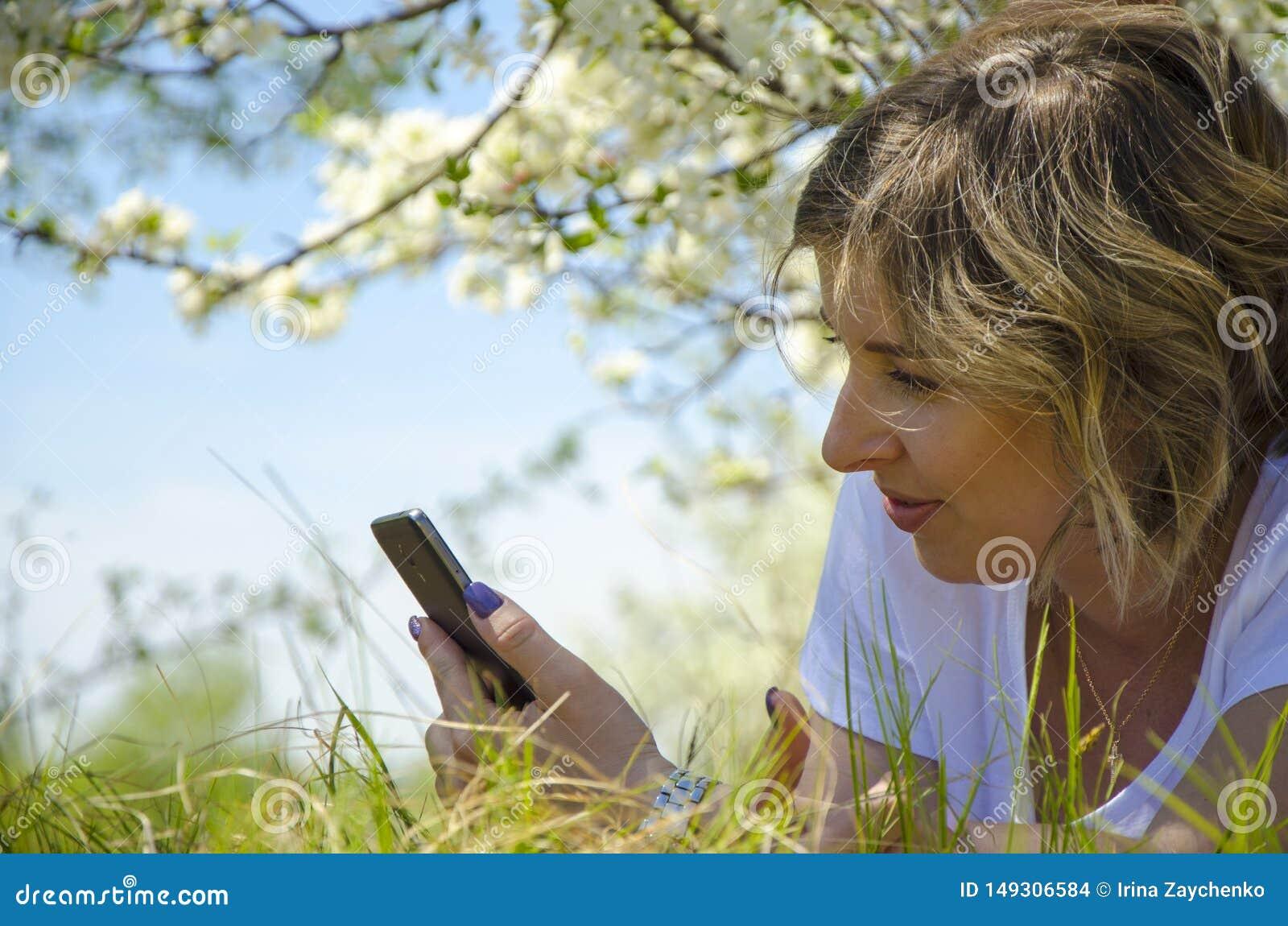 Jovem mulher bonita com um telefone, encontrando-se no campo, na grama verde e nas flores Aprecie fora a natureza Encontro de sor