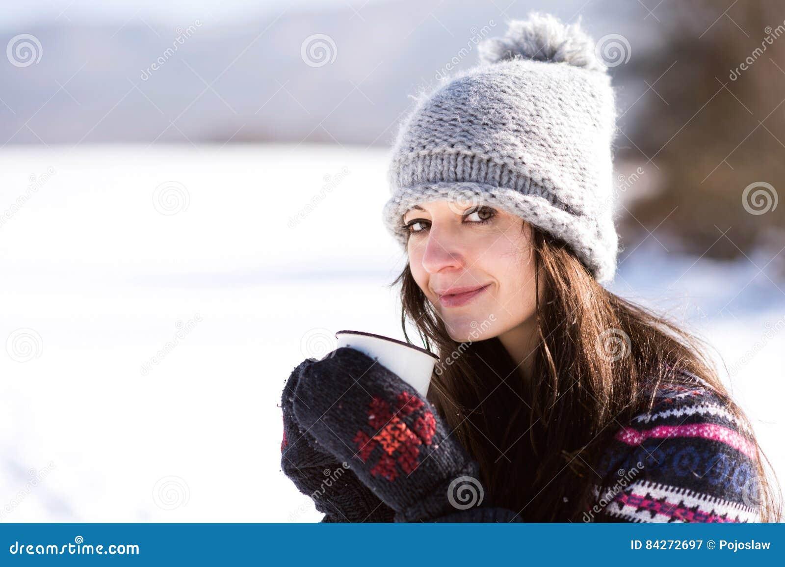 Jovem mulher bonita com a xícara de café na natureza do inverno