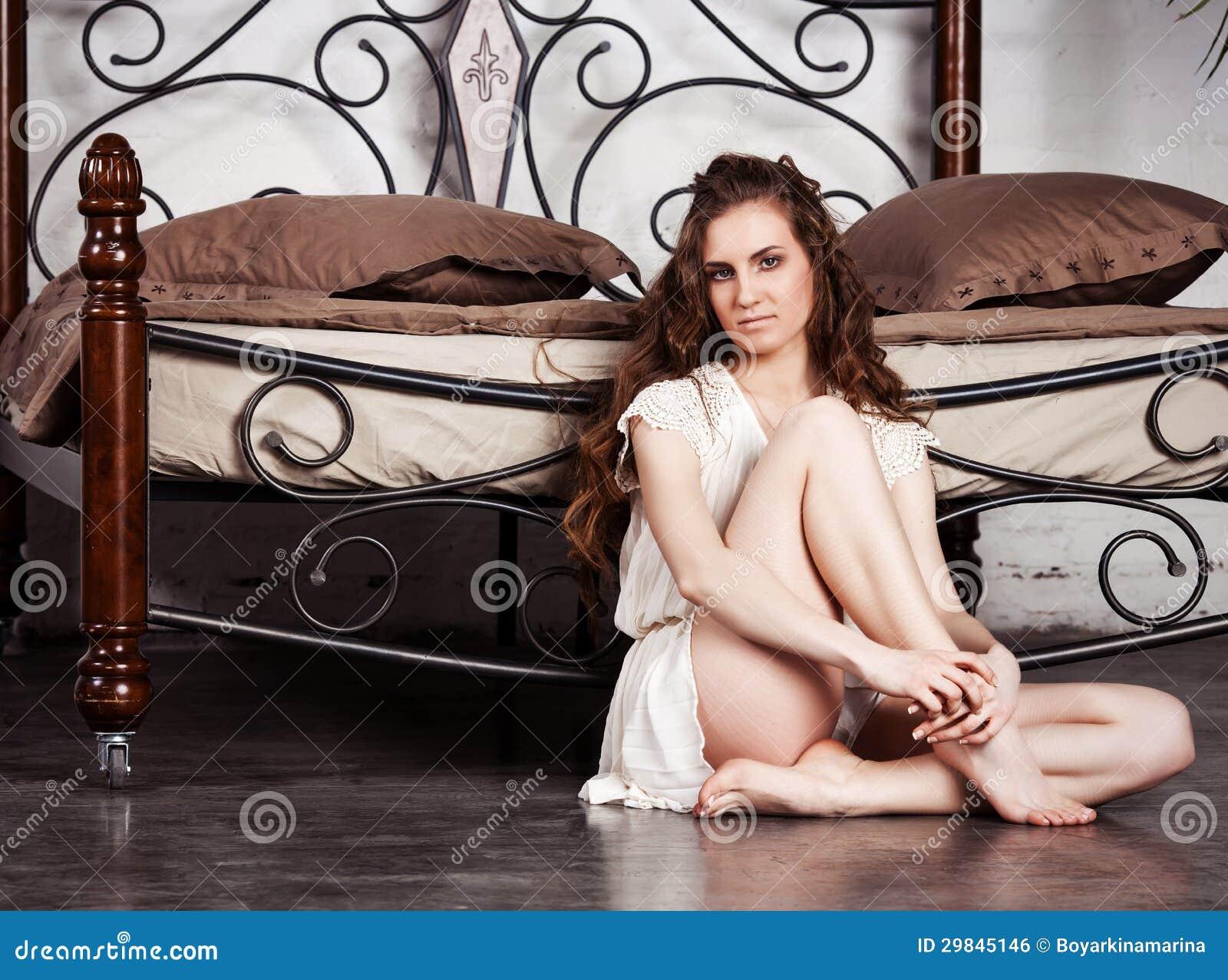 Jovem mulher bonita contra a cama