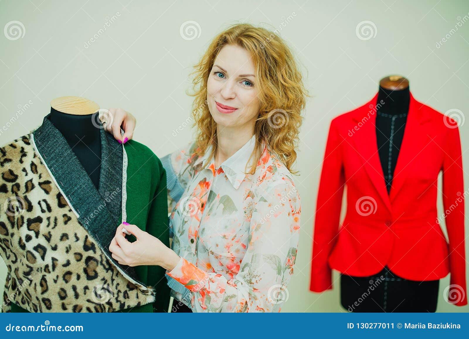 259c23e0a23dc A jovem mulher bonita costura o revestimento do desenhista Revestimento e  verde da cópia do leopardo No fundo é um manequim com um revestimento  vermelho