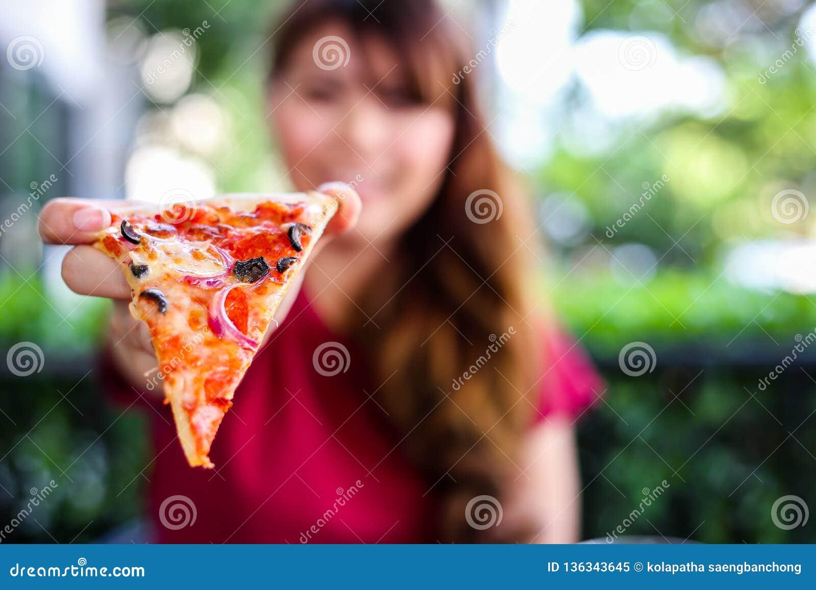 A jovem mulher bonita de encantamento é guardando e mostrando a pizza deliciosa ou saboroso It's algum alimento italiano popula