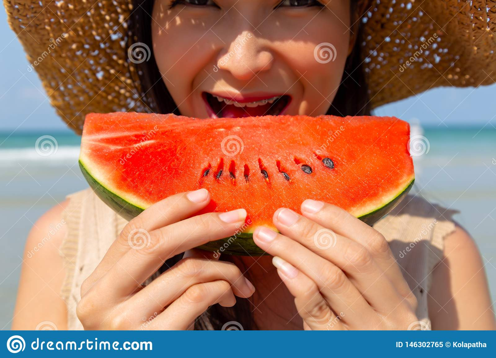 Jovem mulher bonita de encantamento que come a melancia para refrigerar para baixo e extinguir sua sede na temporada de verão na