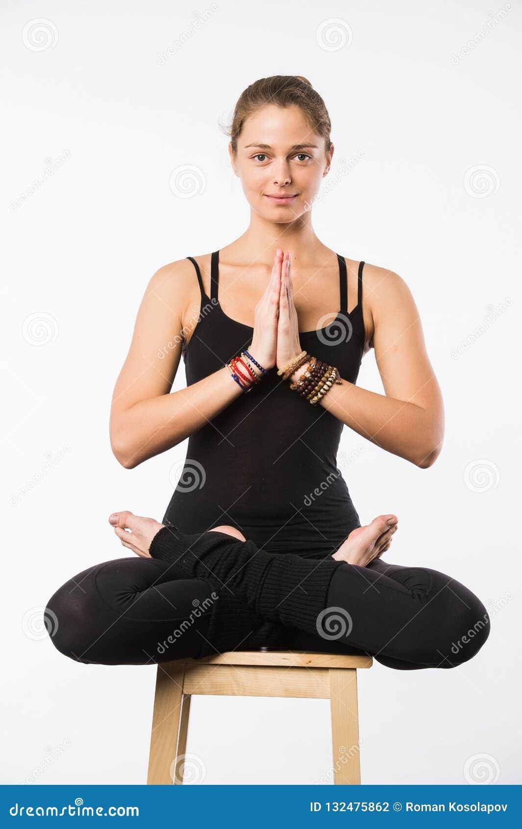 Jovem mulher bonita desportiva que senta-se em Gomukhasana, pose de Cowface, postura do laço da ioga do yin, asana para esticar o