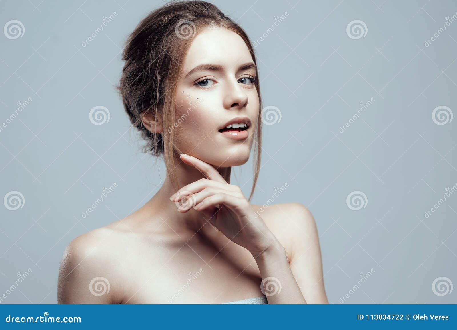 A jovem mulher bonita do close-up com pele fresca limpa toca em sua cara Beleza natural e termas