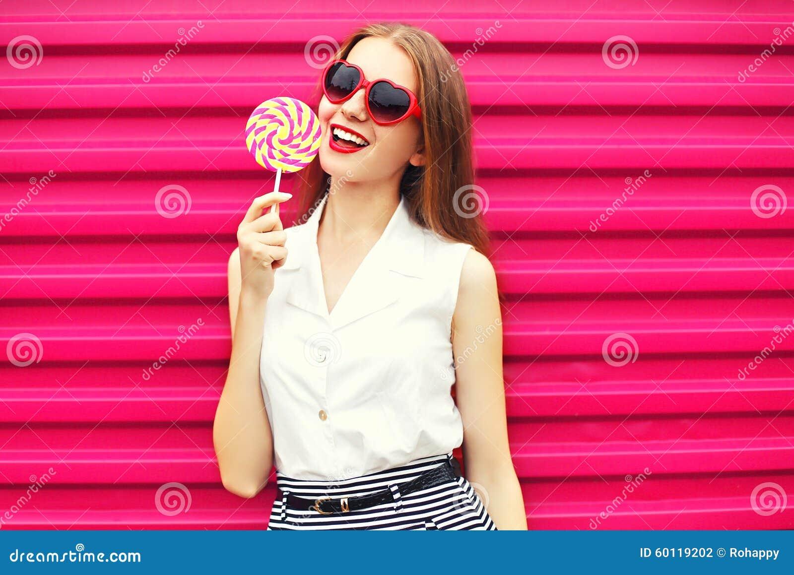 Jovem mulher bonita doce com o pirulito sobre o rosa