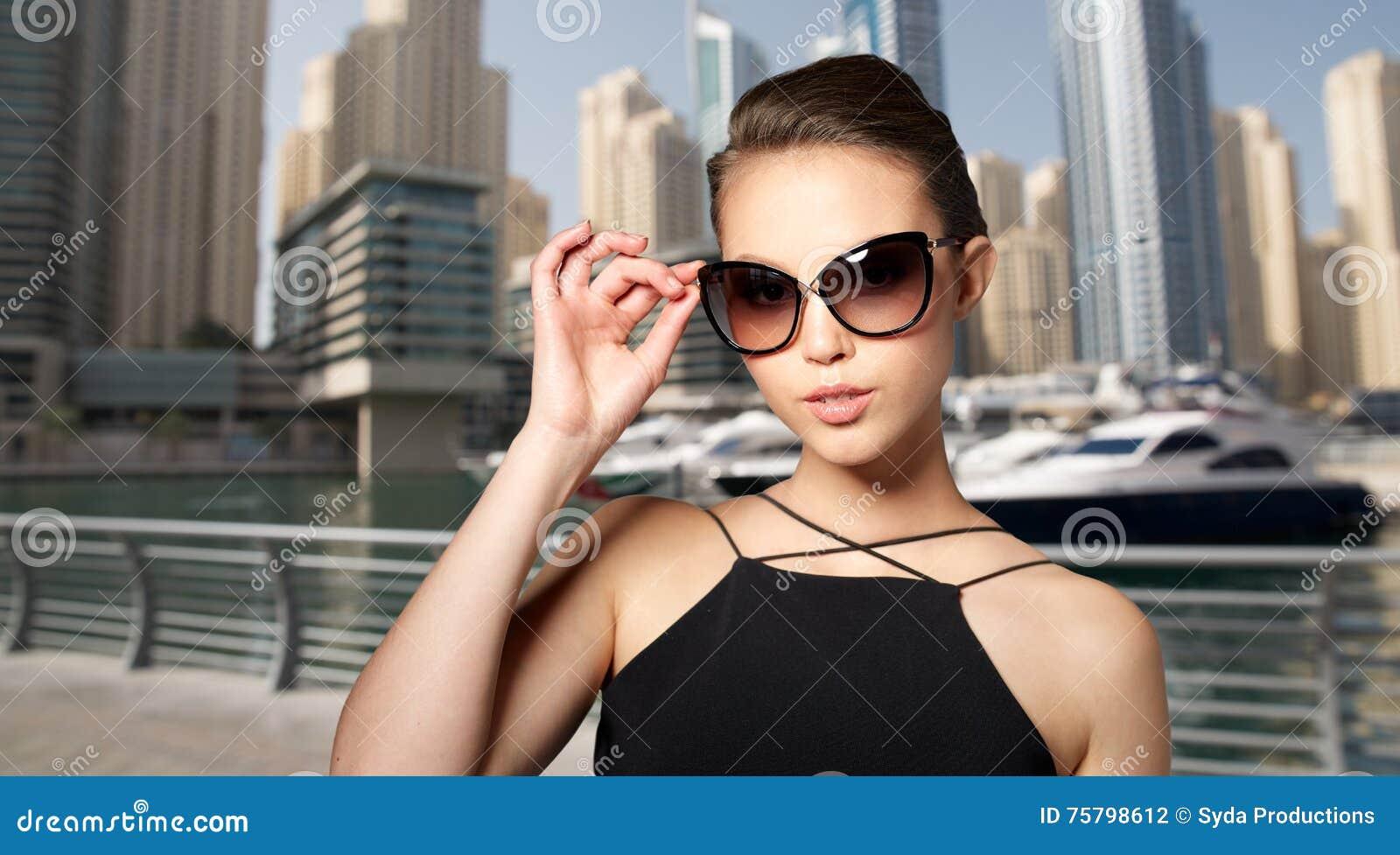 f5e085bac Conceito dos acessórios, do eyewear, da forma, dos povos e do luxo - jovem  mulher bonita em óculos de sol pretos elegantes sobre o fundo do porto da  cidade ...