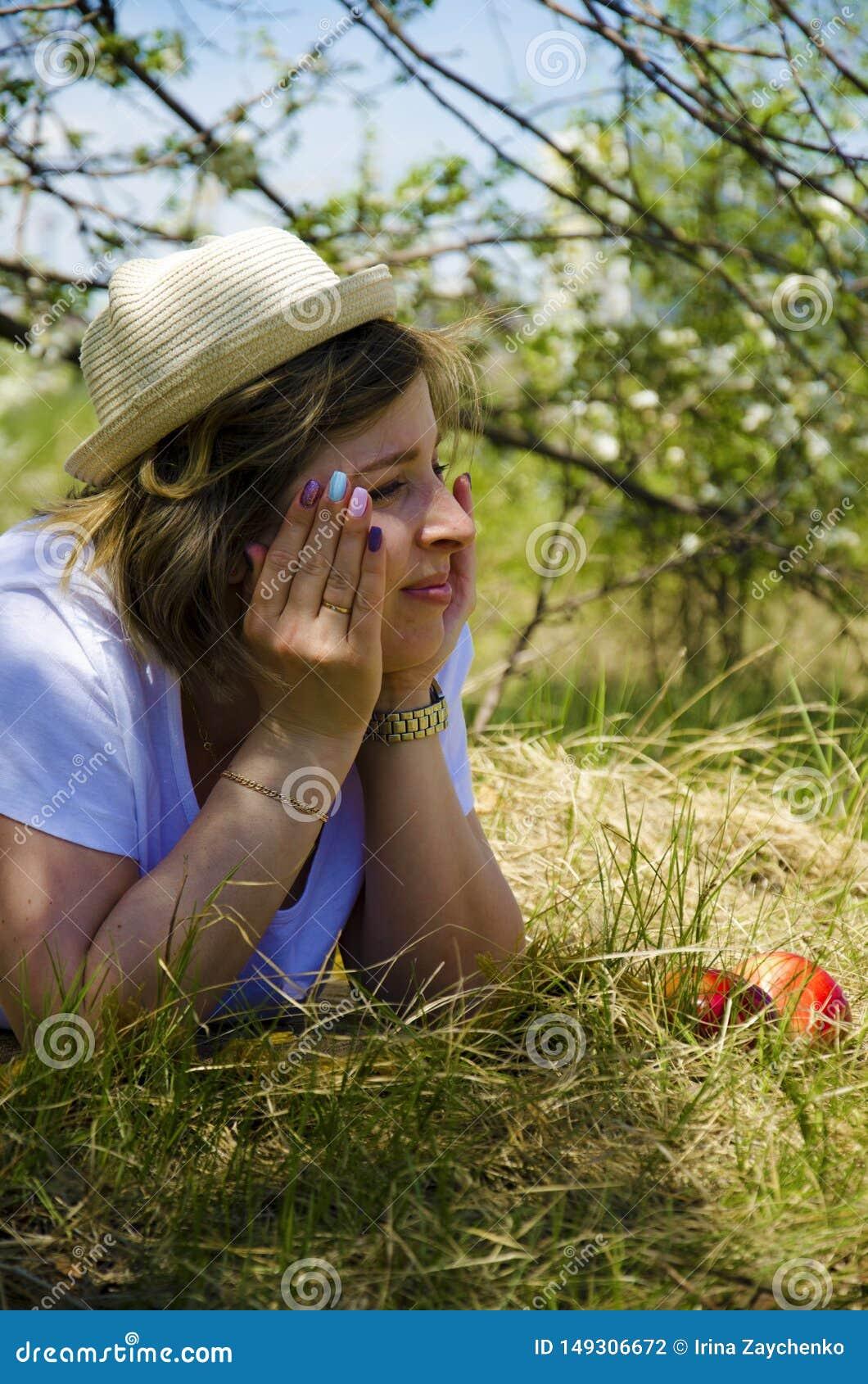 Jovem mulher bonita em um cigarro picado, encontrando-se no campo, na grama verde, nas ma??s e nas flores Aprecie fora a natureza