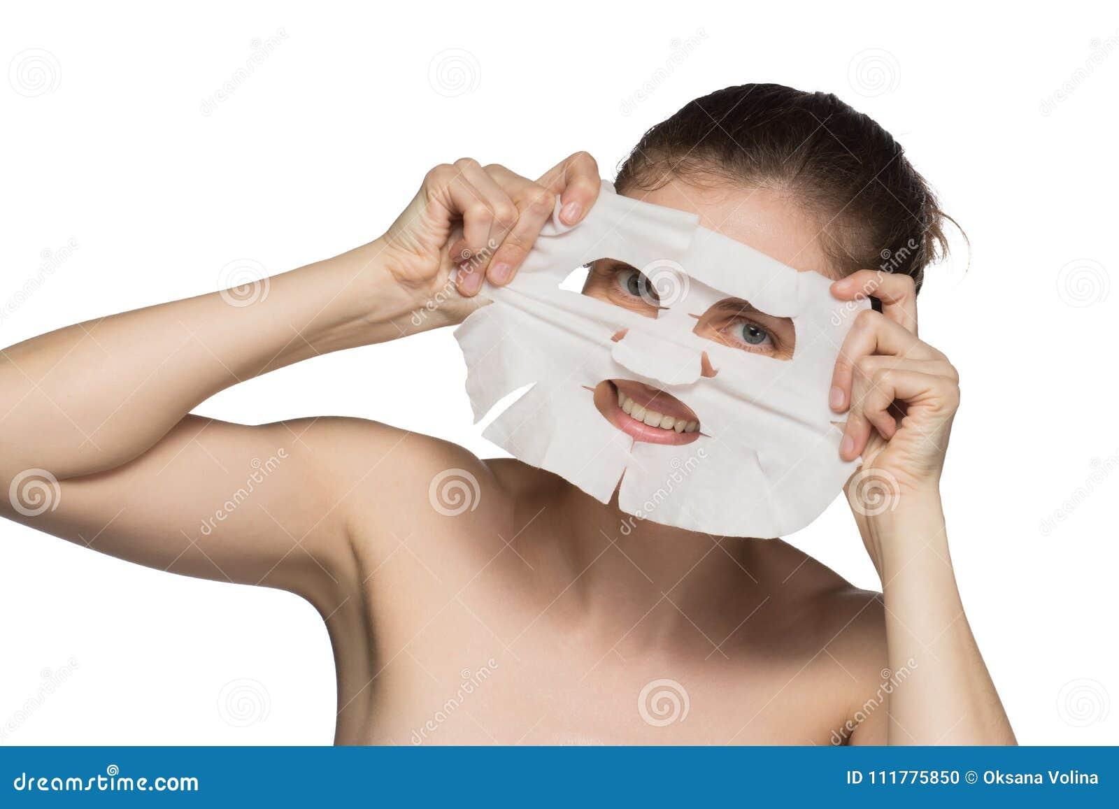 A jovem mulher bonita está aplicando uma máscara cosmética e está sorrindo sobre