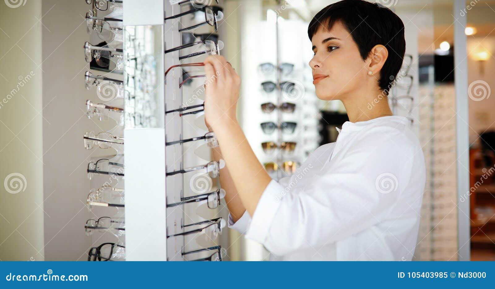 A jovem mulher bonita está escolhendo vidros novos na loja do sistema ótico