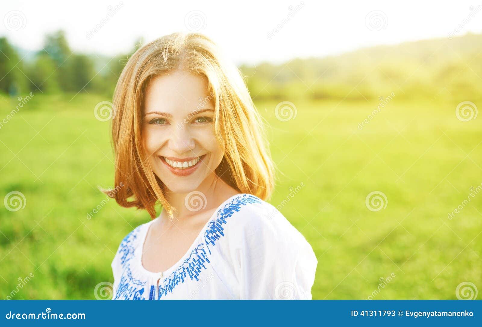 Jovem mulher bonita feliz que ri e que sorri na natureza