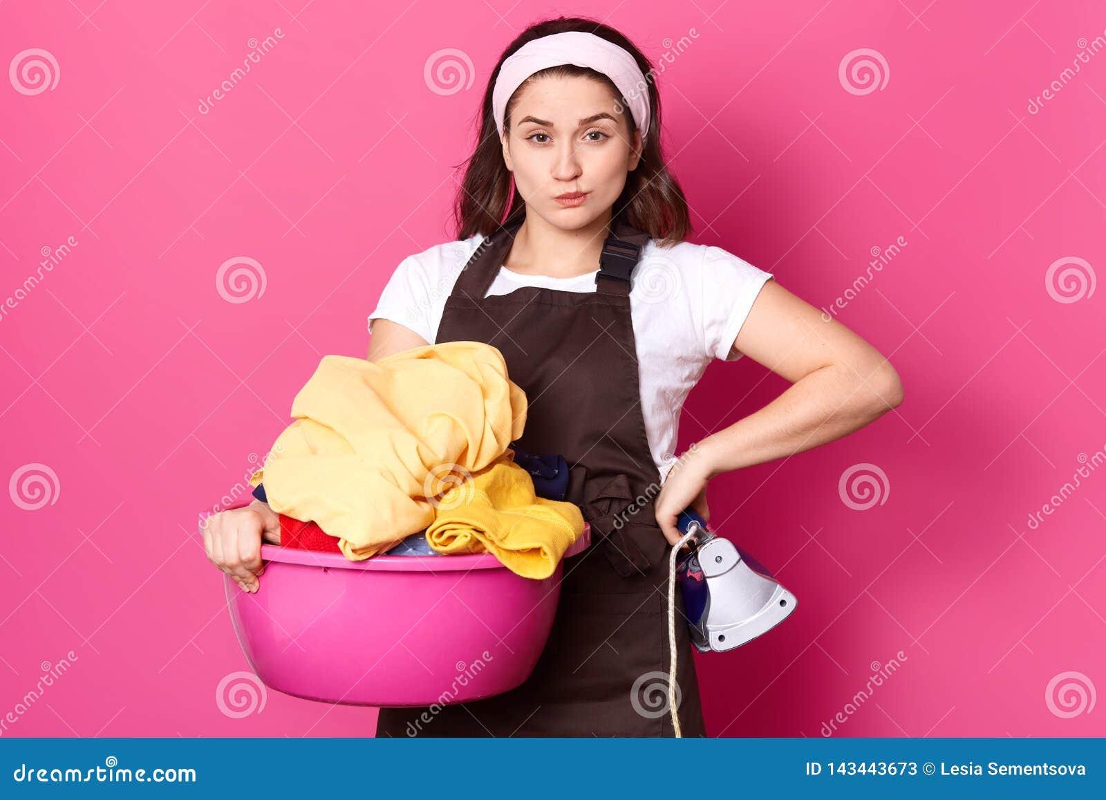 A jovem mulher bonita guarda a bacia cor-de-rosa com a lavanderia e o ferro, olhando a câmera ao estar isolada sobre o fundo cor-