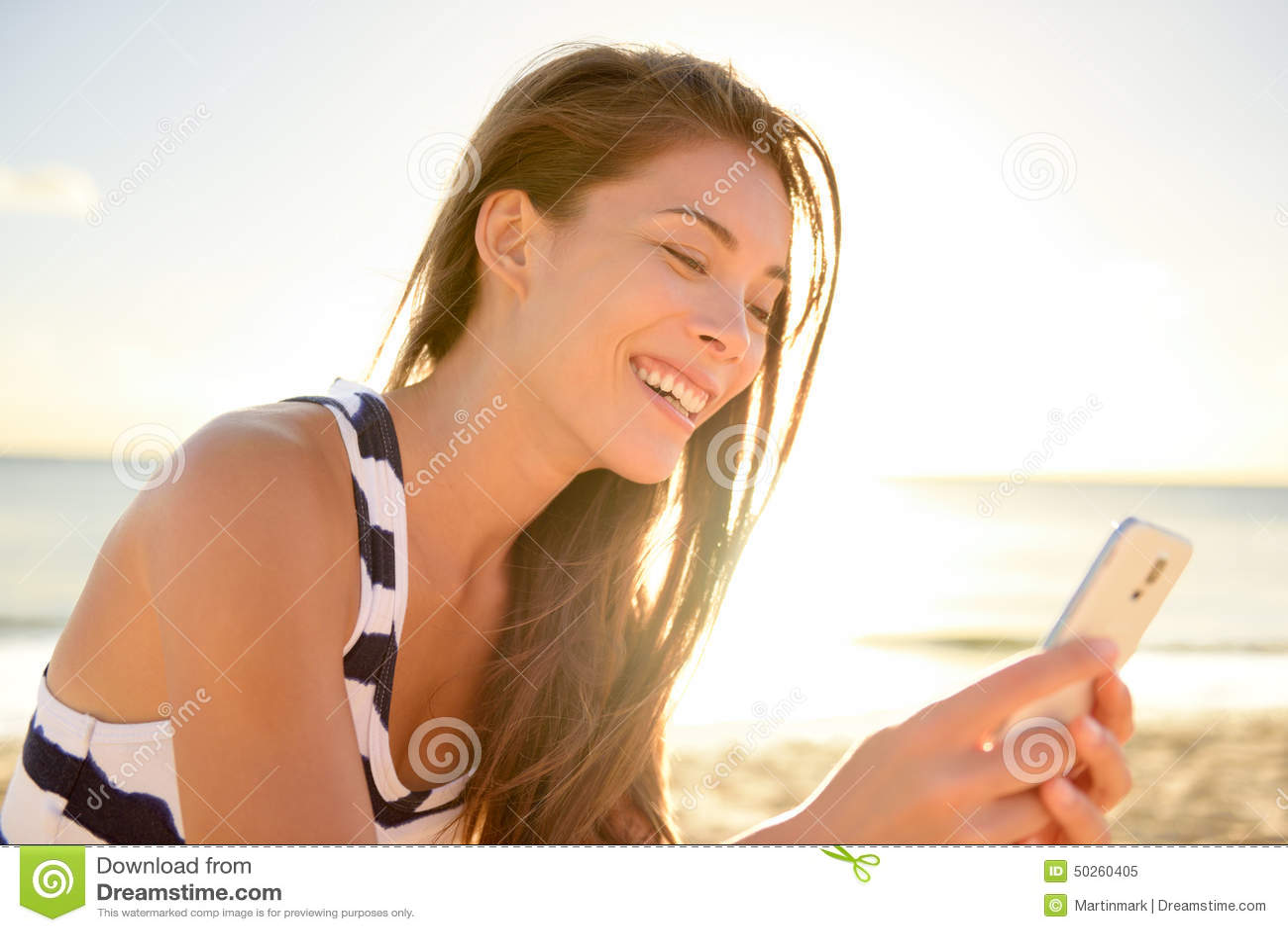 Jovem mulher bonita na praia com telefone esperto