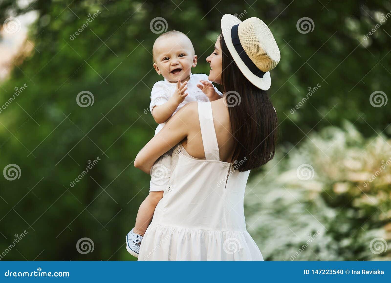 Jovem mulher bonita no chapéu à moda e em um vestido branco com seu filho pequeno bonito na camisa e no short em suas mãos