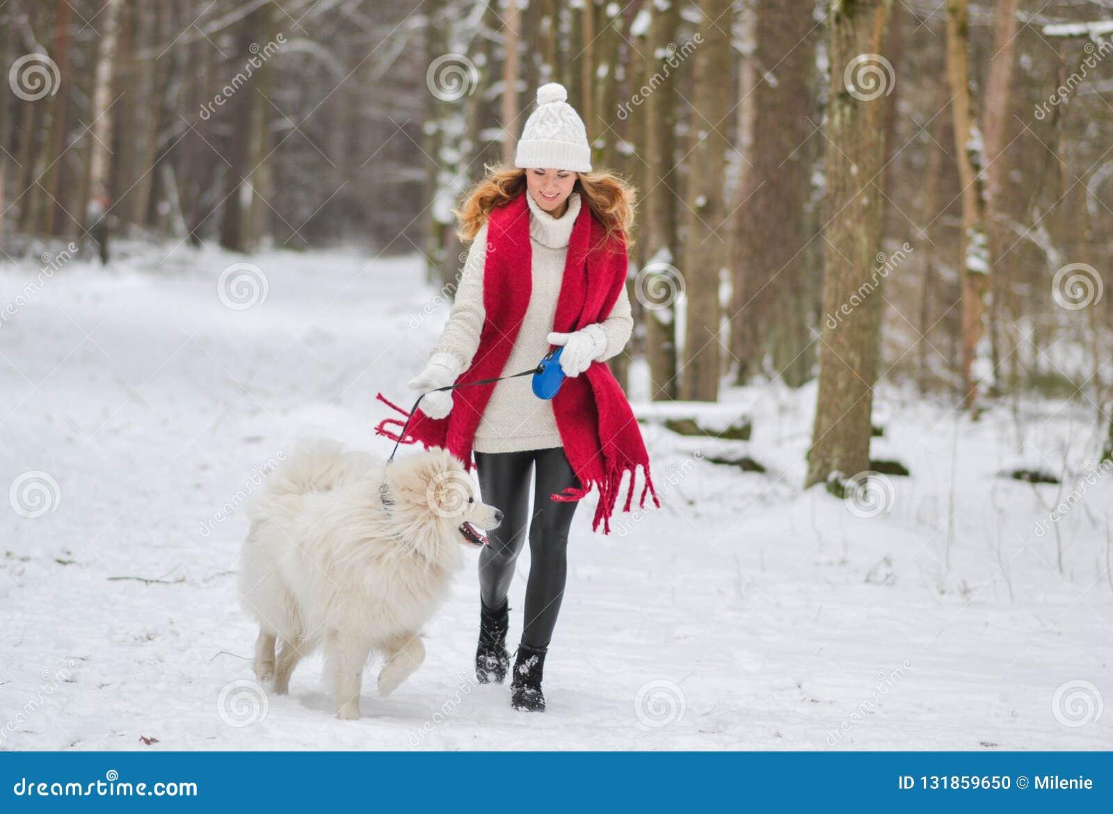 Jovem mulher bonita no inverno nevado Forest Park Walking Playing com seu cão