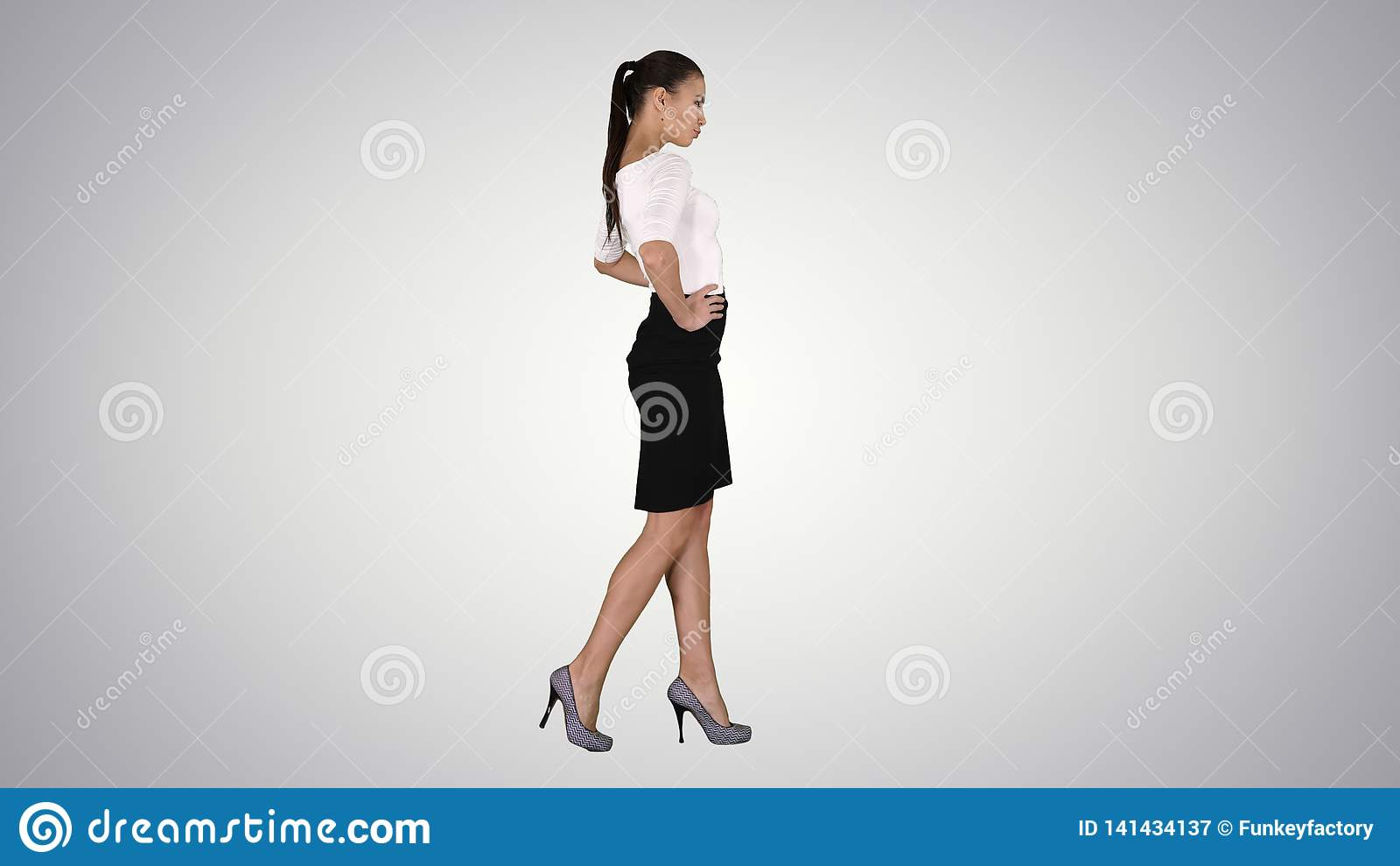 Jovem mulher bonita no passeio elegante do equipamento, guardando as mãos nos quadris no fundo do inclinação