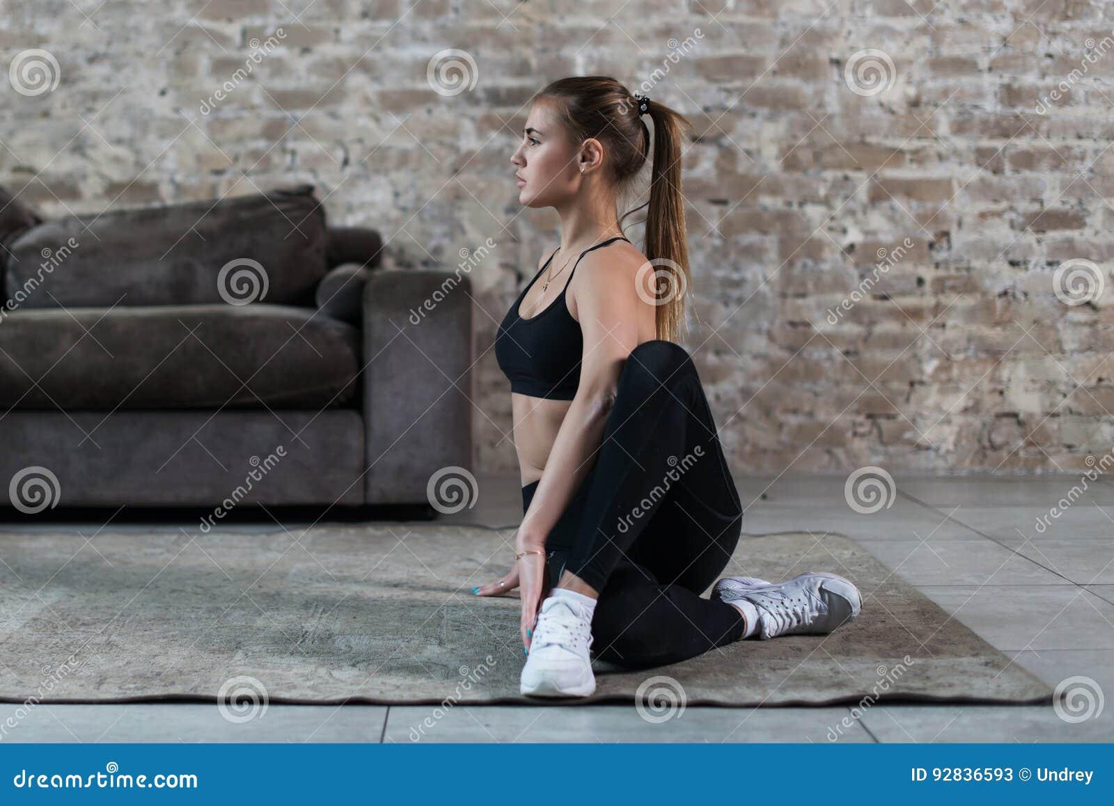 Jovem mulher bonita no sportswear que faz a ioga praticando assentada da torção espinal na sala de visitas