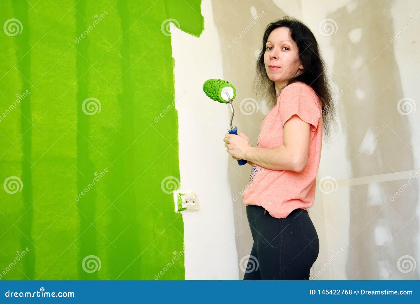 A jovem mulher bonita no t-shirt cor-de-rosa é de sorriso e de mantimento o rolo, pintando a parede interior verde em uma casa n