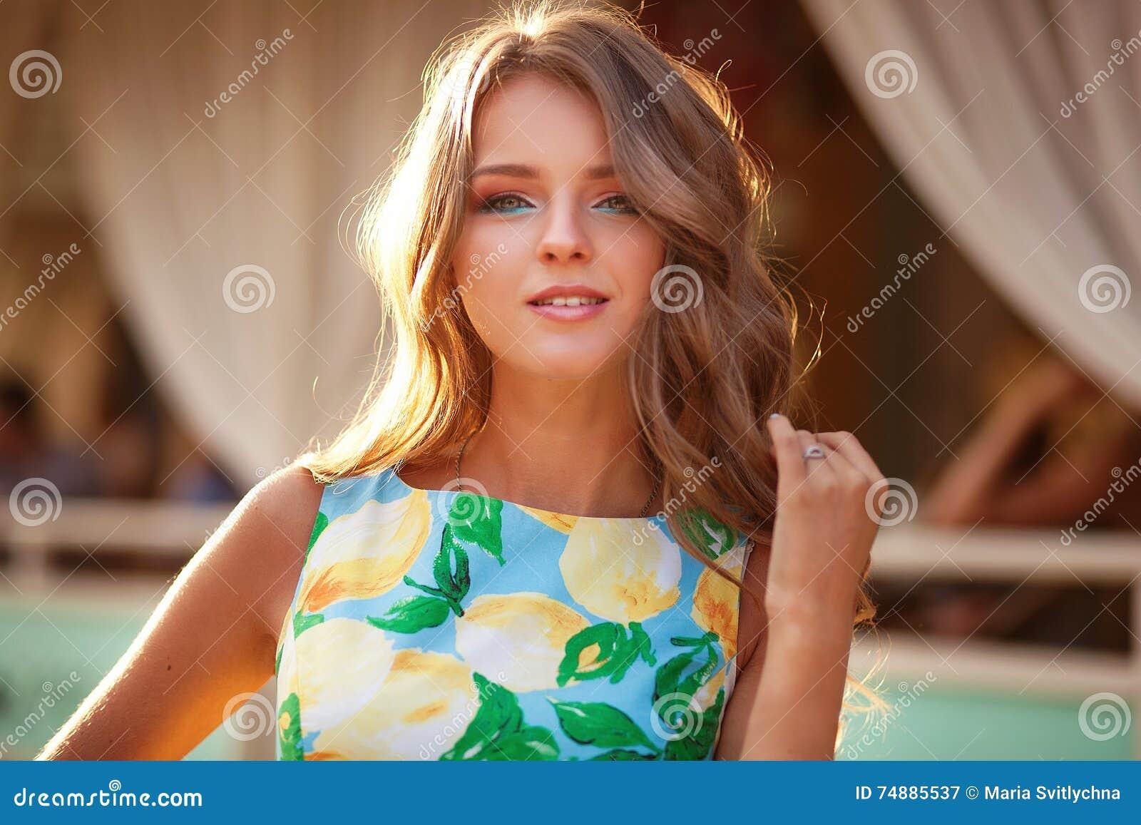 Jovem mulher bonita que anda na noite ensolarada da cidade Feliz e