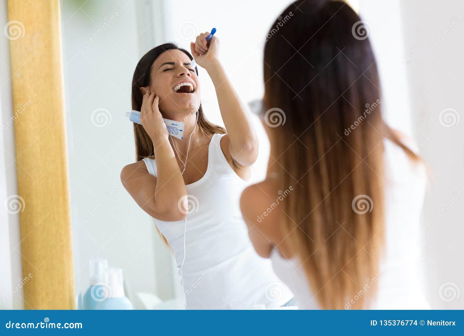 Jovem mulher bonita que aprecia o tempo ao escovar seus dentes no banheiro em casa