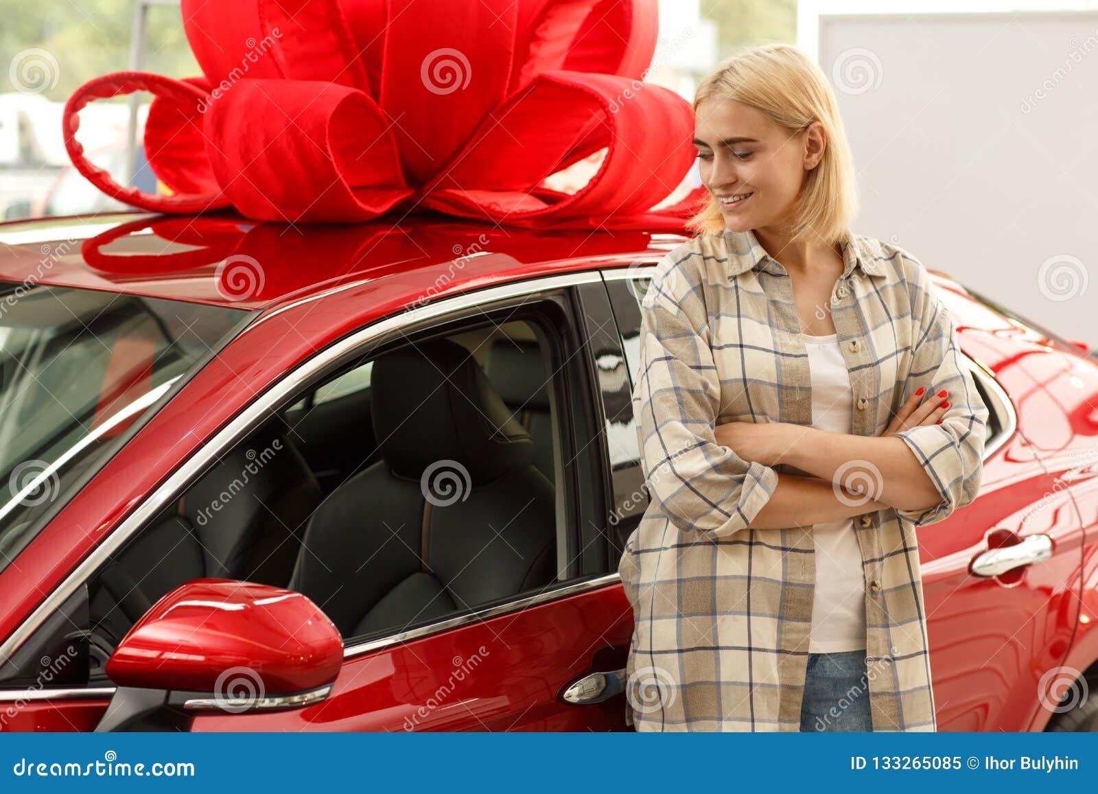 Jovem mulher bonita que compra o carro novo no negócio