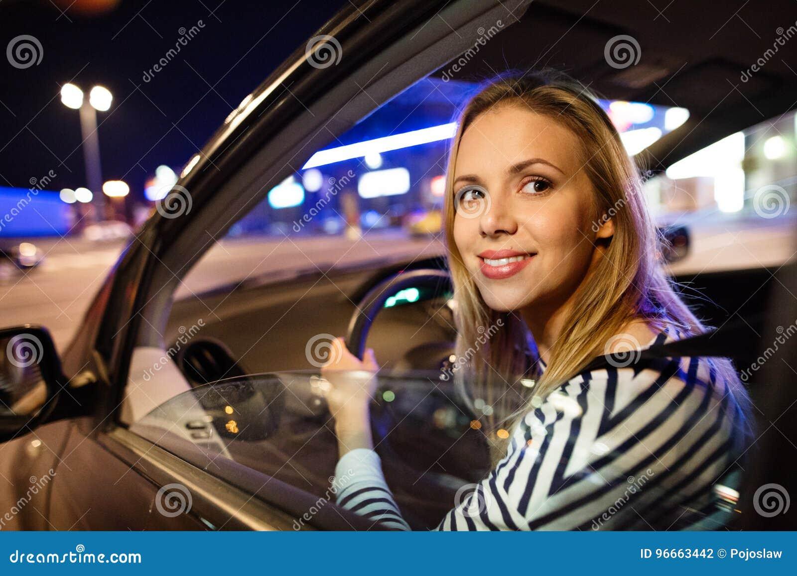 Jovem mulher bonita que conduz seu carro na noite