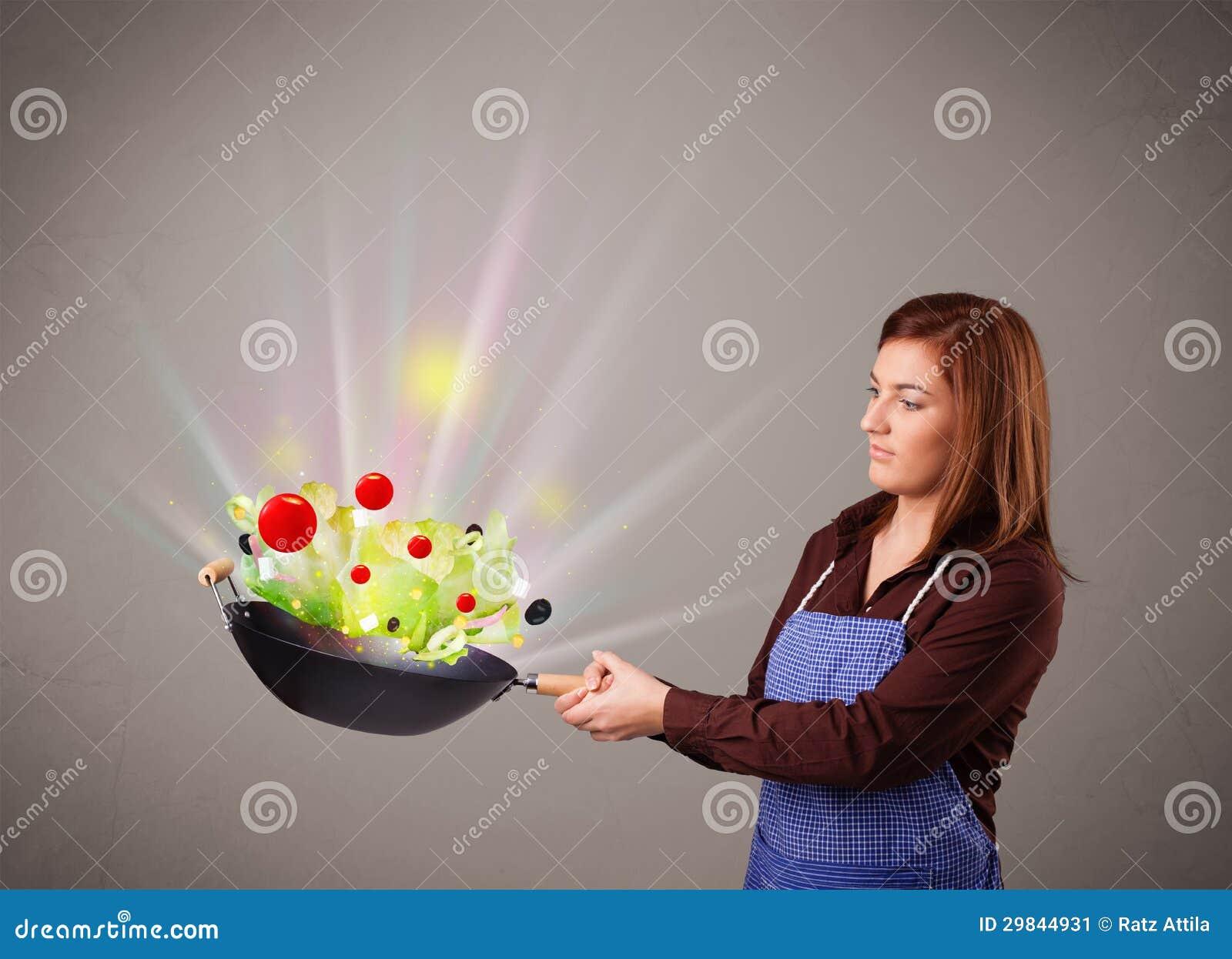 Jovem mulher que cozinha legumes frescos
