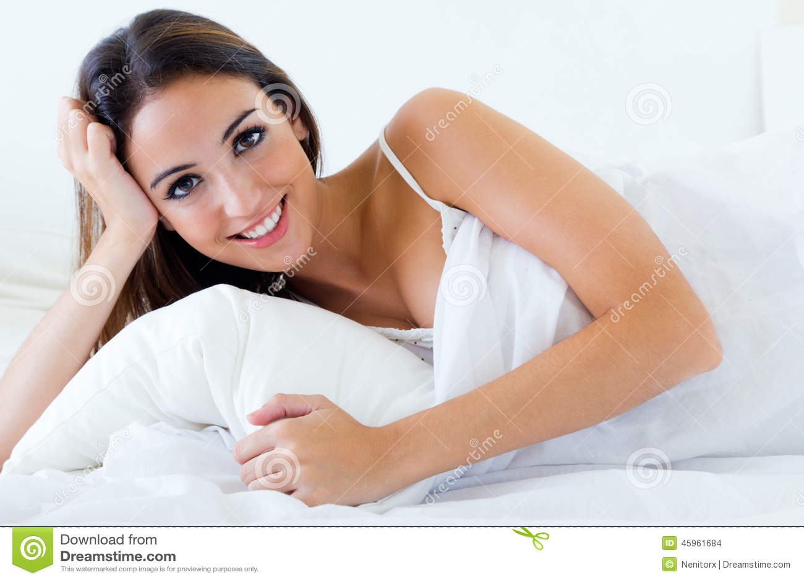 Jovem mulher bonita que encontra-se na cama Isolado no branco