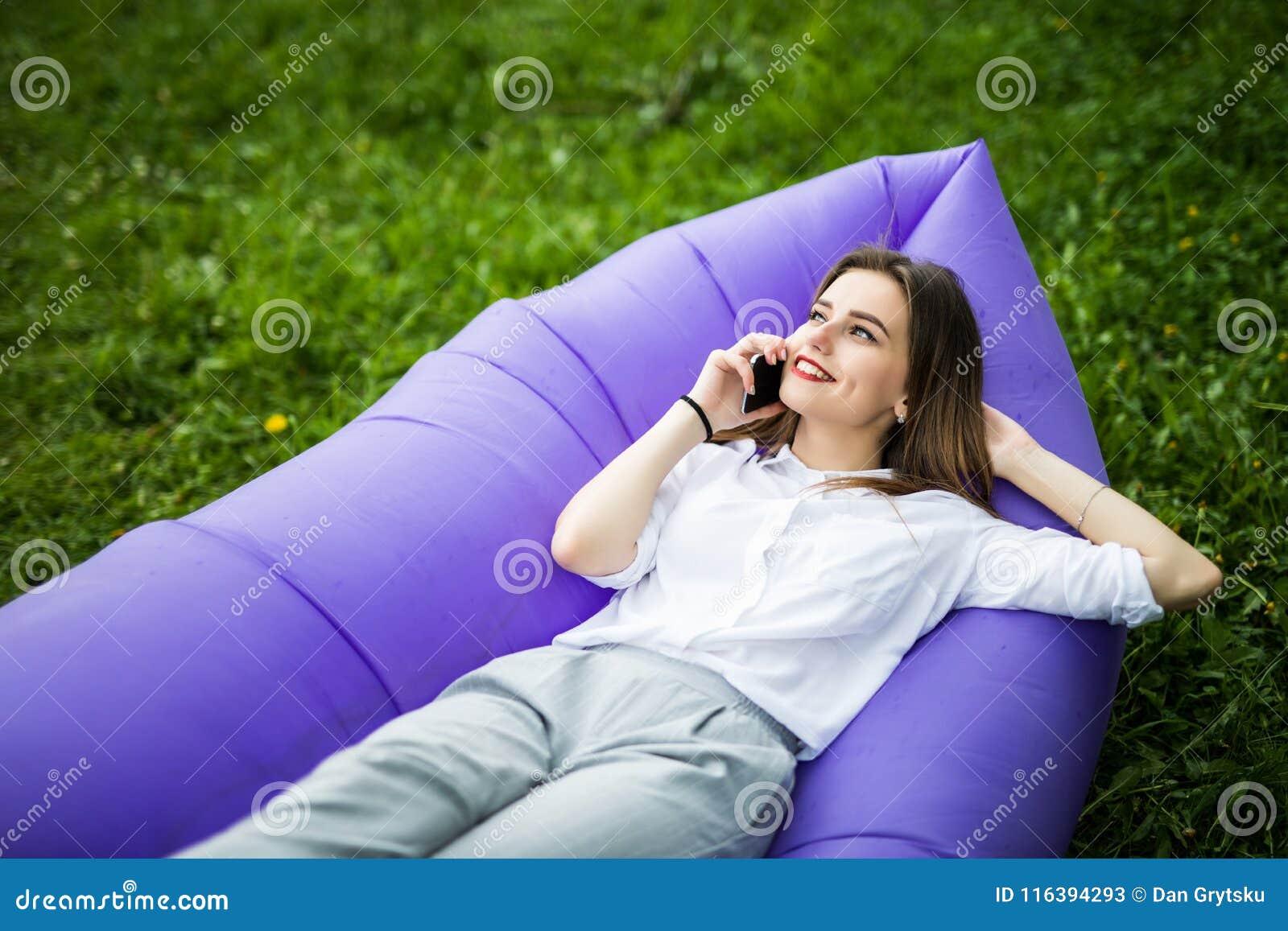 Jovem mulher bonita que encontra-se na conversa inflável do lamzac do sofá no telefone ao descansar na grama no parque