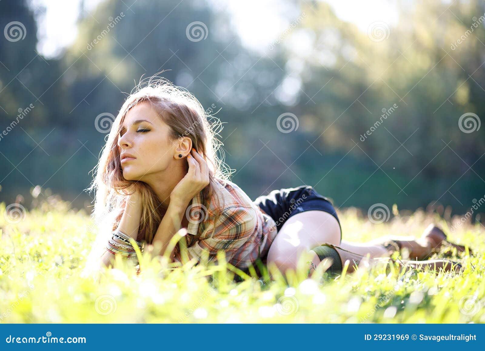 Download Jovem Mulher Bonita Que Encontra-se Na Grama Imagem de Stock - Imagem de elegante, se: 29231969