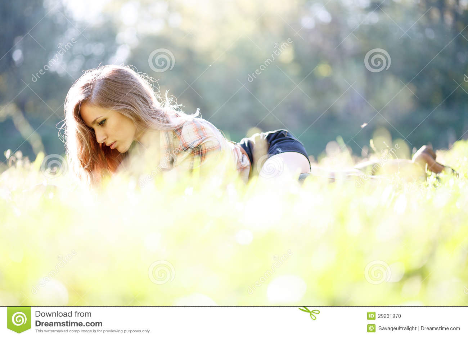 Download Jovem Mulher Bonita Que Encontra-se Na Grama Foto de Stock - Imagem de consideravelmente, descanso: 29231970