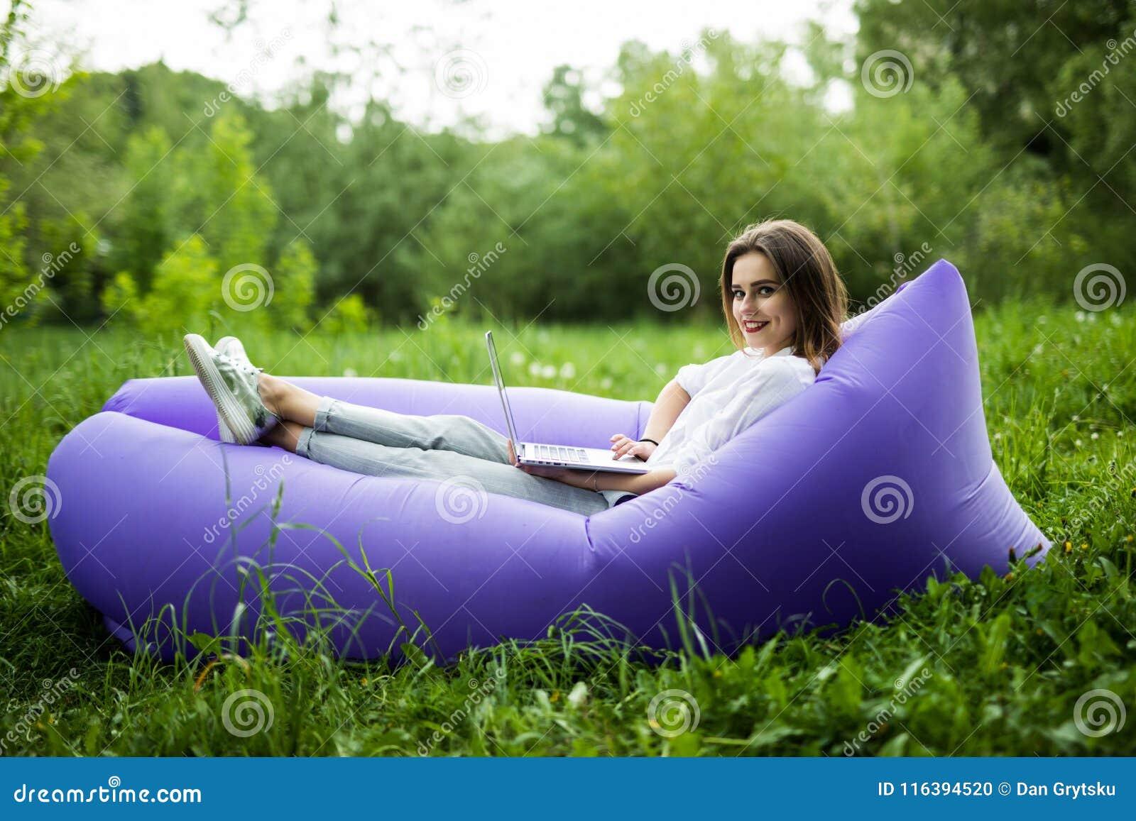A jovem mulher bonita que encontra-se no lamzac inflável do sofá consulta no Internet no portátil ao descansar na grama no parque