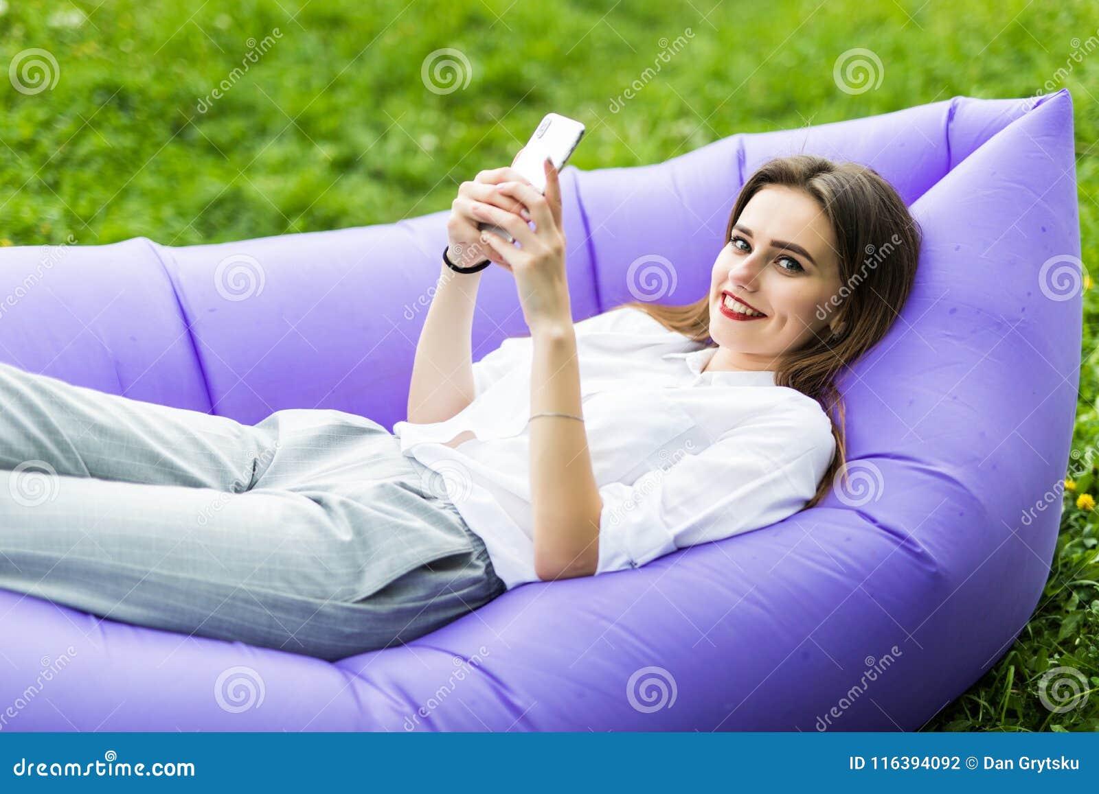 A jovem mulher bonita que encontra-se no uso inflável app do lamzac do sofá do telefone, consulta o Internet ao descansar na gram
