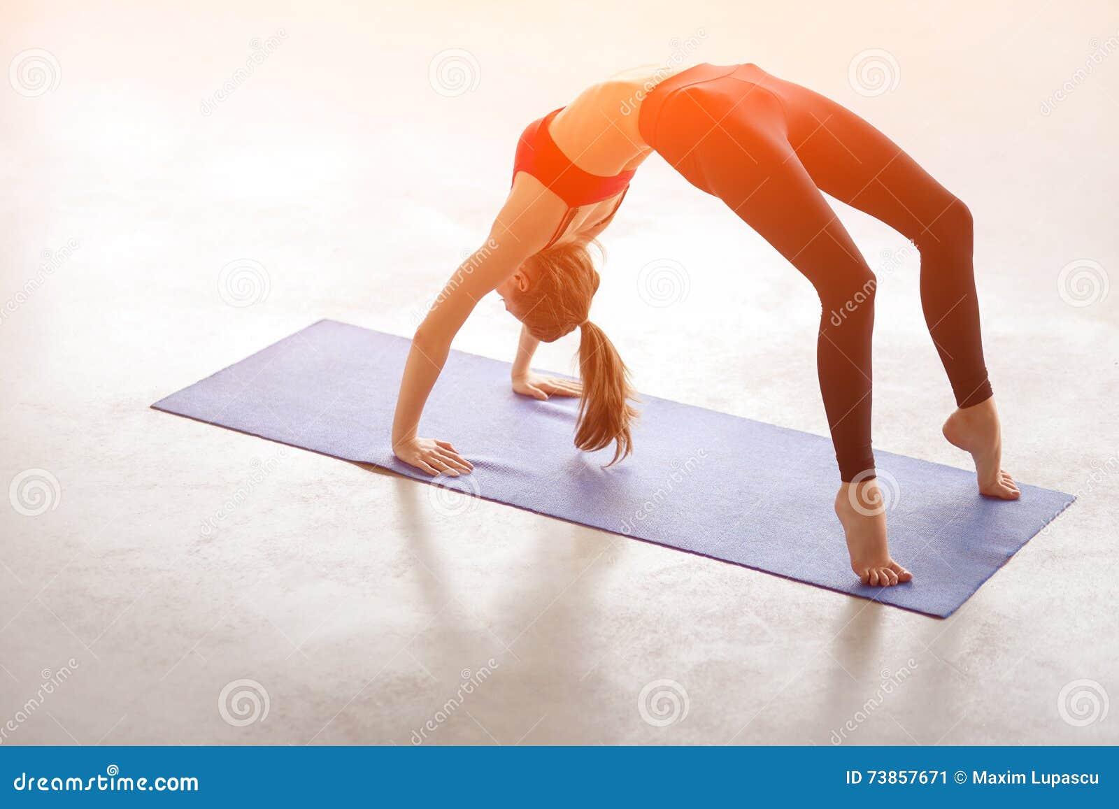 Jovem mulher bonita que faz a pose da ponte do exercício da ioga