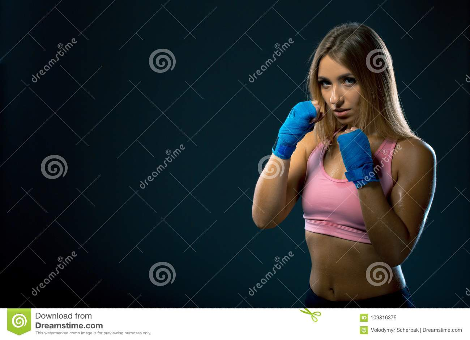 Jovem mulher bonita que levanta em um suporte do encaixotamento Menina suado nas ataduras do encaixotamento após a formação em um