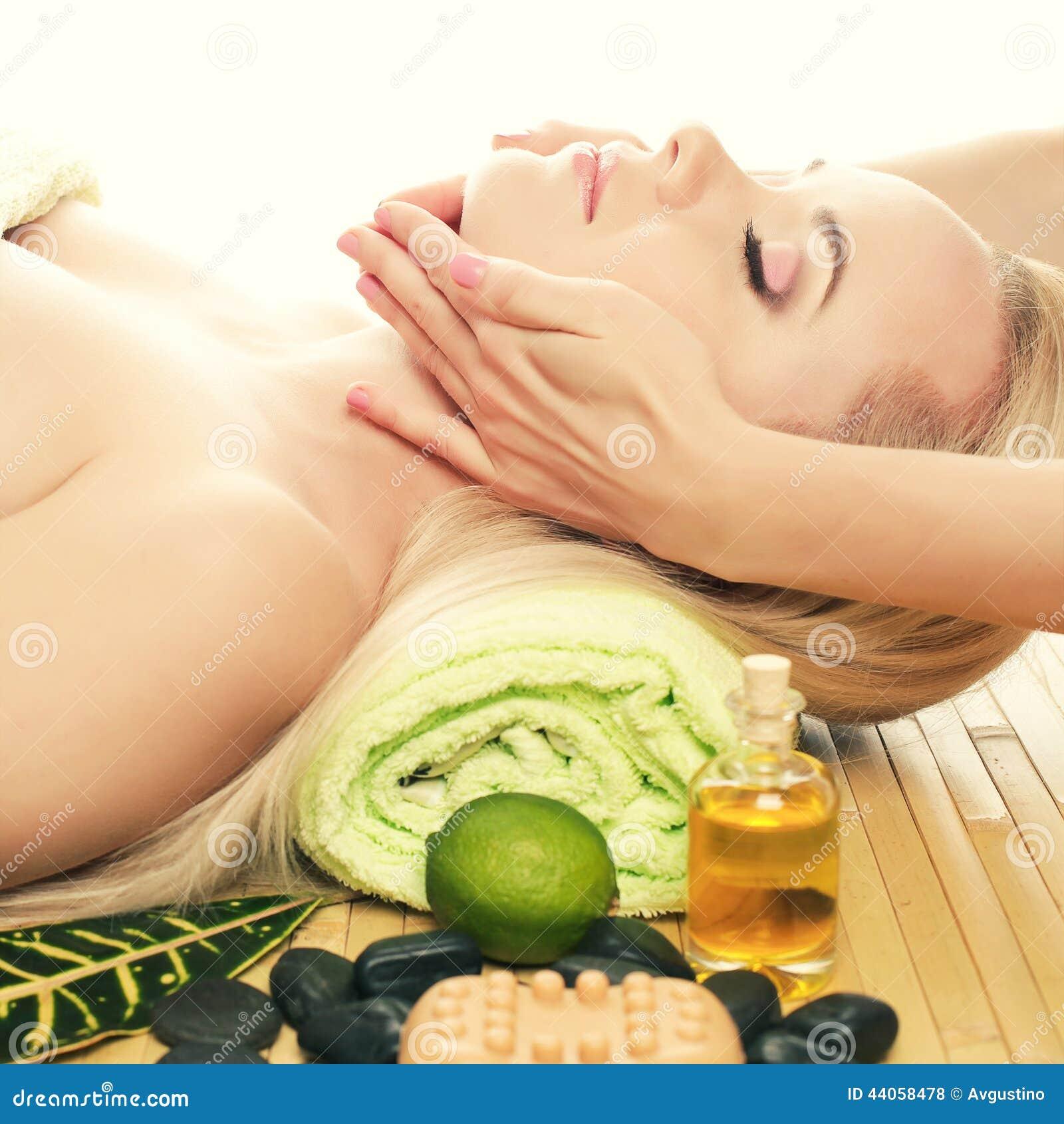 Jovem mulher bonita que recebe a massagem facial em um salão de beleza dos termas