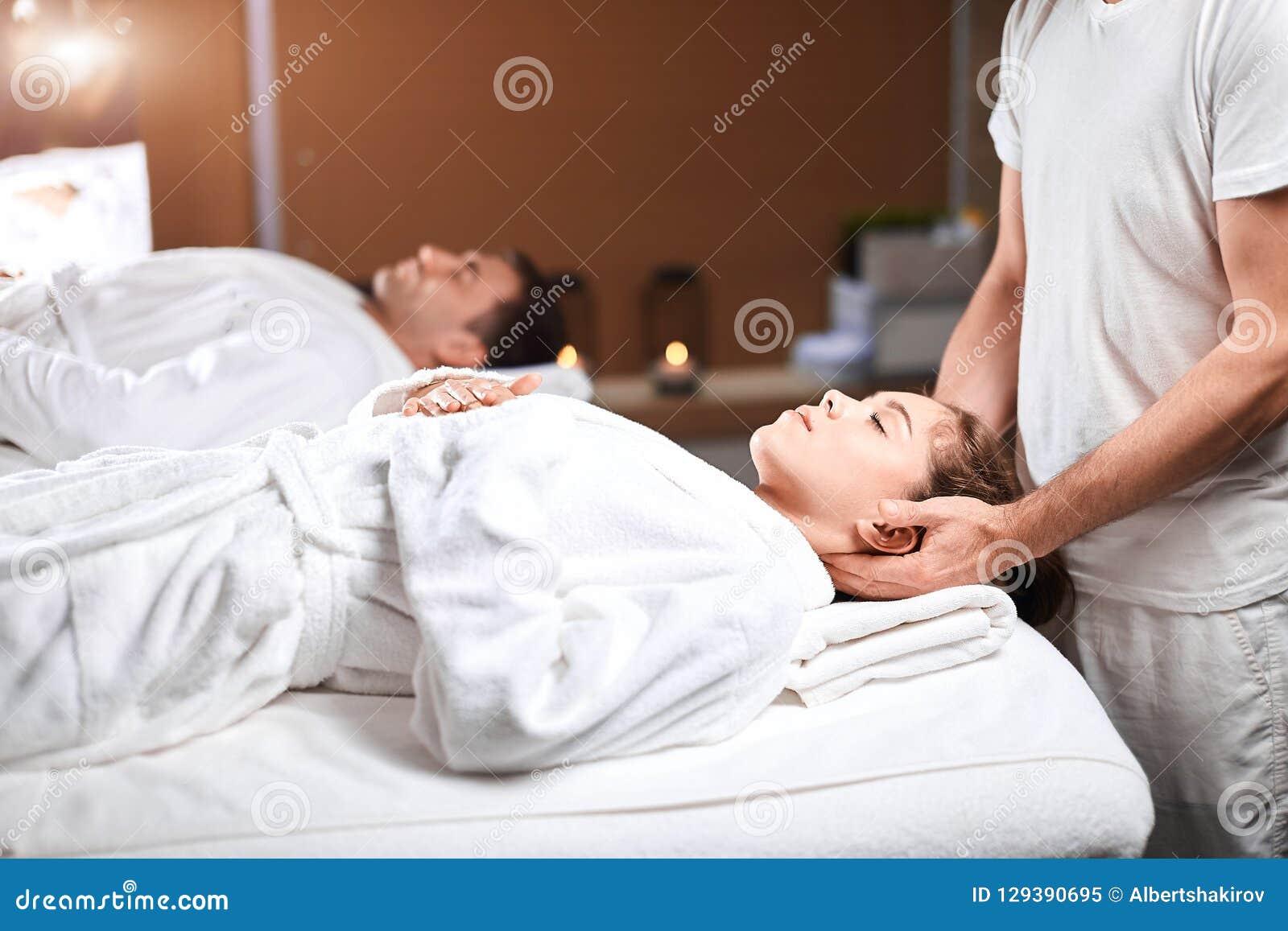 Jovem mulher bonita que recebe a massagem na zona principal e dos ombros no centro dos termas