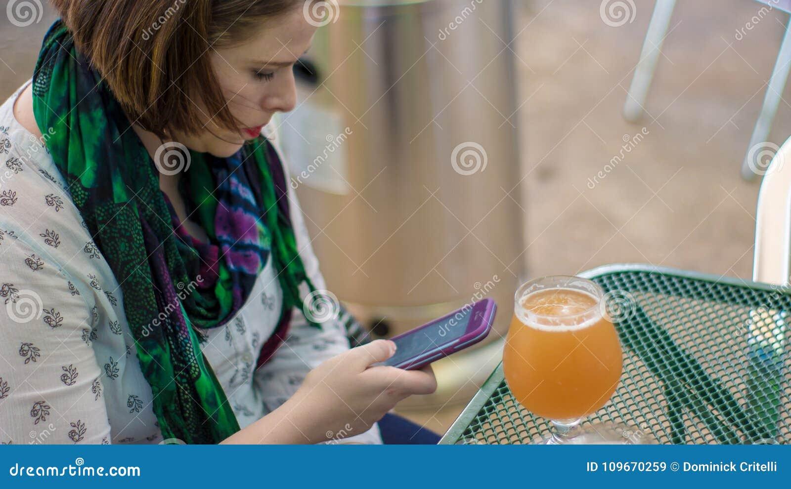 Jovem mulher bonita que senta-se em uma tabela com uma cerveja que datilografa um te