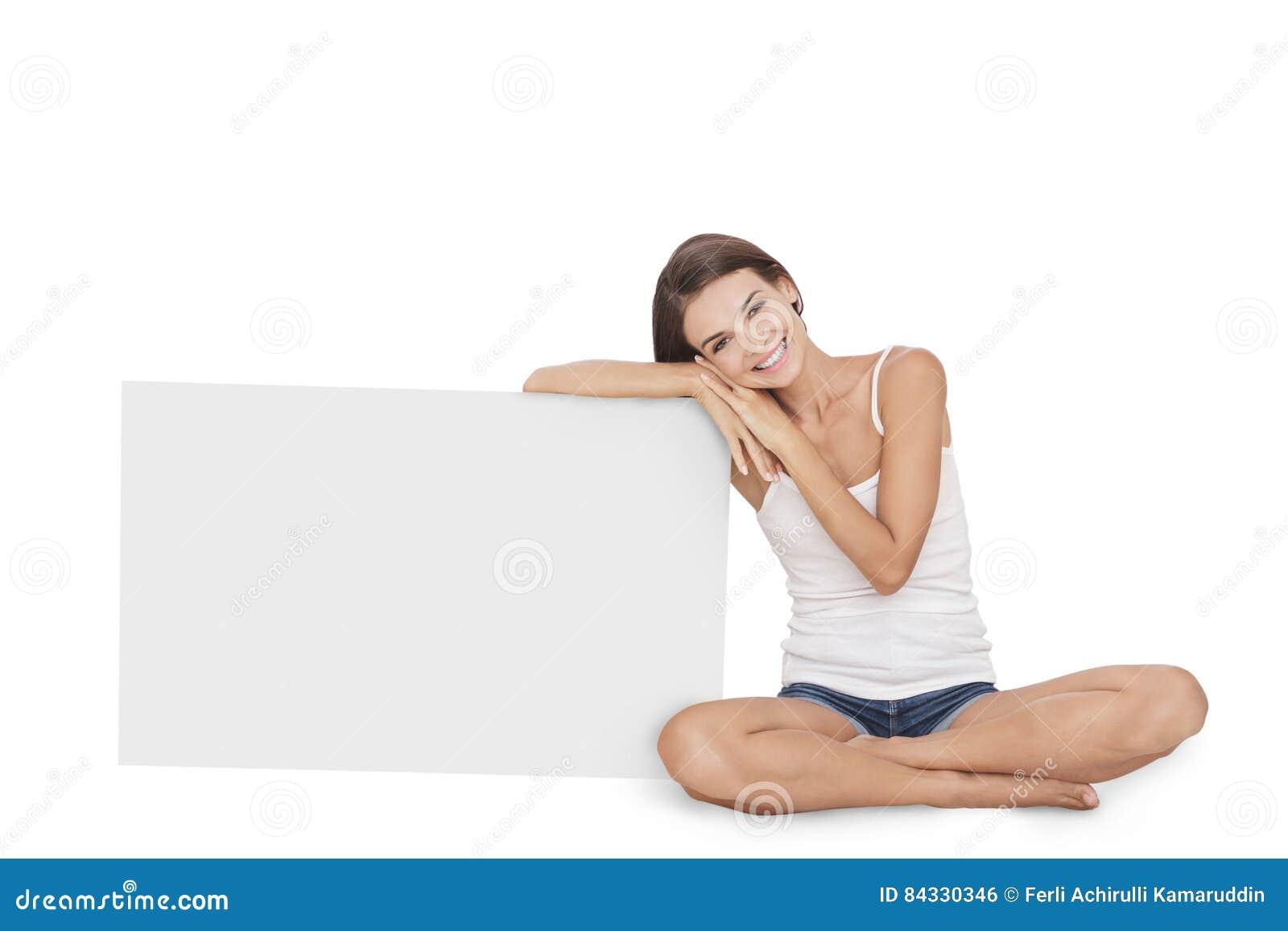 Jovem mulher bonita que sorri ao inclinar-se na placa vazia
