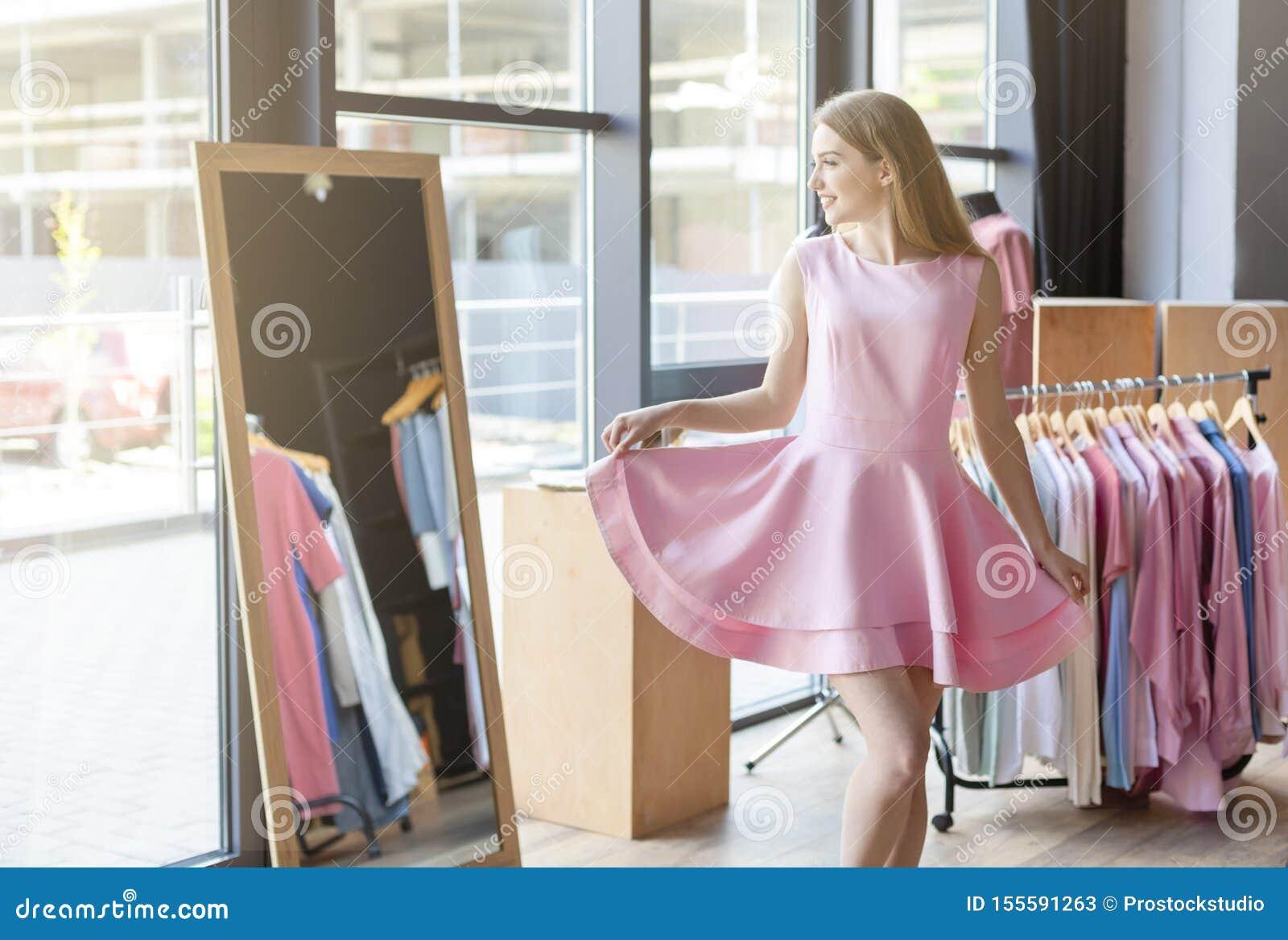 Jovem mulher bonita que tenta o vestido cor-de-rosa na frente do espelho