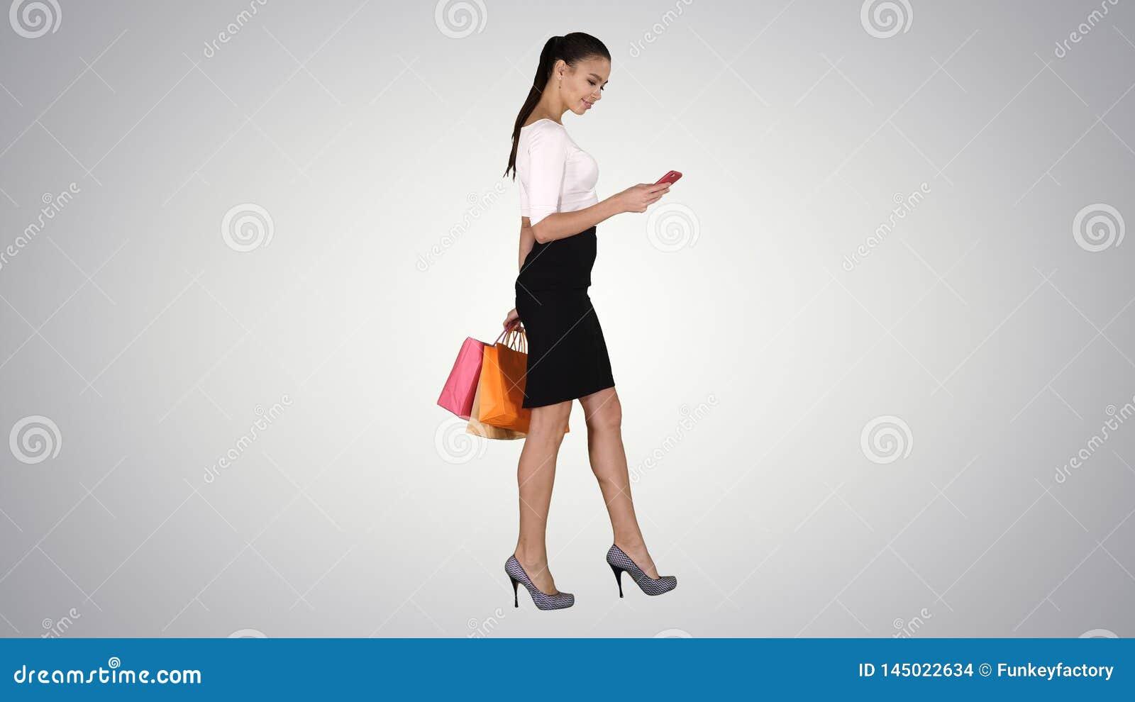 Jovem mulher bonita que usa um telefone celular que anda e que guarda sacos de compras no fundo do inclina??o