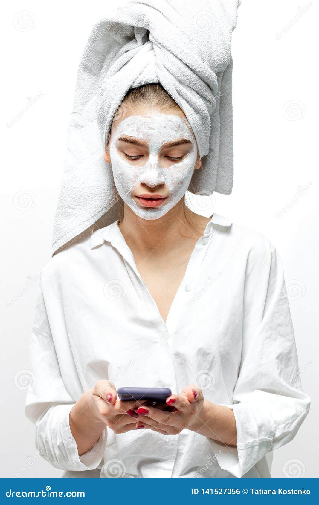 A jovem mulher bonita vestida na roupa branca com uma toalha branca em seu cabelo e máscara cosmética em sua cara guarda móvel