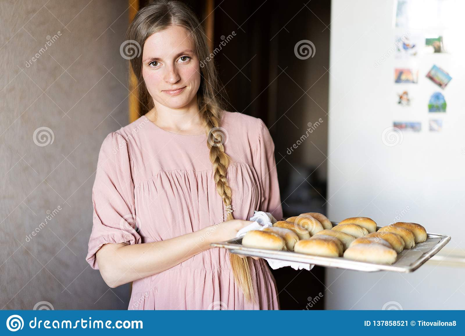 Jovem mulher bonito em um vestido cor-de-rosa com uma foice na cozinha perto do refrigerador a senhora em sua cozinha Uma dona de